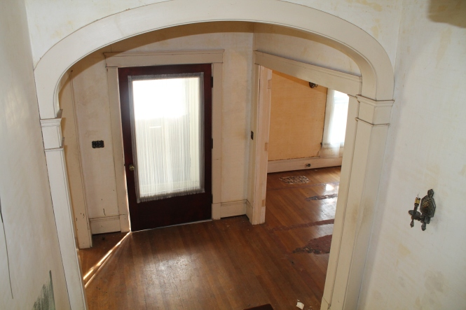 Looking down from the stairwell to the front entry.  To the left, the living room.  To the right, the dining room.